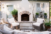 An outdoor fireplace with wicker furniture