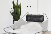 This is a metal and leather statement armchair decorated with sheepskin.
