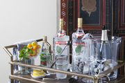A brass-hued bar cart in front of a decorative cabinet.
