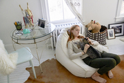 A girl's room with a Serena & Lily beanbag, cowhide rug, sheepskin-covered chair, and vintage table