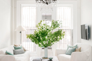 A white living room with a vase full of greenery.