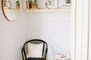 A small corner with a black chair and green and white wallpaper.