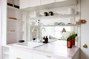 A compact kitchen with white shelving