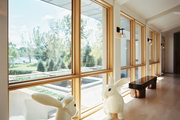 Oversize rabbit sculptures in front of a wall of windows