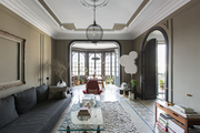 A pendant lamp above a glass-topped coffee table; arched doorway and curved architectural detail