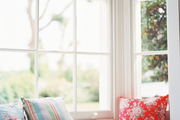 A window seat with floral and striped pillows