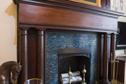 Traditional dark wood and blue tile fireplace.