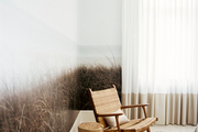 Nature-inspired wallpaper in a room with a woven chair and a wood side table