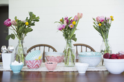 A detail of a tablescape with pastel bowls and florals.