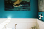 Blue walls and nautical decorations in a bathroom with a corner sink