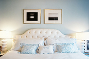 A tufted white headboard flanked by a pair of white lamps