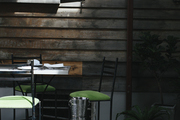 Outdoor dining area with rustic wood siding metal seating.