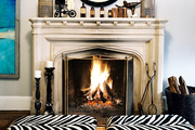 A convex mirror above a fireplace and a pair of zebra-print ottomans