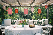 Paper lanterns suspended above a bench of pillows and an oval dining table