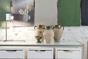 Vintage lockers and a metal lamp next to urns on a CB2 console and file cabinets
