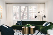 This living room has a green velvet couch, a black accent chair, and a brass coffee table.