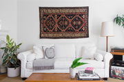 A contemporary living room with a hanging antique rug.