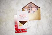 A gold, pink, and red invitation for a Wes Anderson themed holiday party