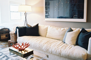 A white couch and a transparent trunk atop a chevron rug