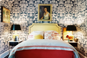 Chinoiserie wallpaper covering the walls and ceiling of a room with an upholstered bed