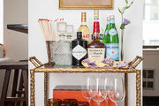 A three-tiered bar cart holds libations and glassware