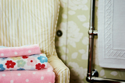 A striped armchair in a bathroom with floral wallpaper