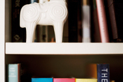 A white horse figurine on a white bookshelf