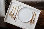 A dinner tray with gold flatware