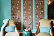 A trio of vintage-wallpaper panels behind a pair of armchairs and a garden stool