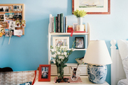 A faux-bamboo bedside table topped with a blue-and-white lamp and a tray of accessories