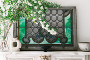 A stained glass window pane on a marble mantel.