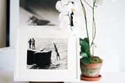 Framed photography and an orchid on a white surface