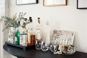 A tray of bar essentials and decorative accessories atop a black demilune table