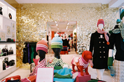 An array of kate spade new york merchandise against a wall of gold paillettes