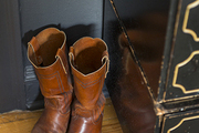 Vintage boots next to a set of drawers against a wall of chalkboard paint