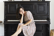 Rachel Bilson at her antique piano topped with a mermaid sculpture and a collection of framed art