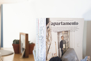 A collection of interior design magazines with an artful book end on a wood desk.