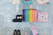 A lucite shelf with colorful decor in a kid's room.