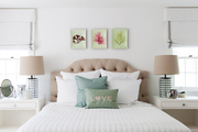 A tufted headboard flanked by white bedside tables