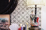 Around black mirror above a desk topped with a colorful textile and a vintage lamp