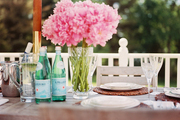 Fresh peonies, woven rattan placemats, and crystal wine glasses set the tone for sophisticated alfresco dining.