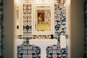Blue-and-white wallpaper and a white pedestal sink in a bathroom