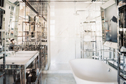 A freestanding tub in a mirrored bathroom