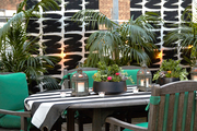 An outdoor dining table and chairs with a canopy and curtains on Irene Edwards's rooftop patio