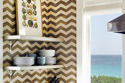A kitchen with walls covered in chevron tile