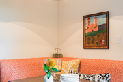 A kitchen nook with an orange booth and a drum light.