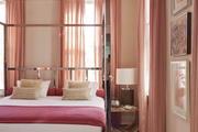 A four-poster chrome bed surrounded by shades of pink and peach