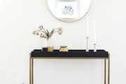 A black side table with gold ceramic pieces and a circular mirror hanging above it.