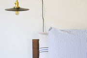 An industrial wall sconce beside a bed