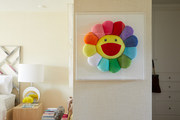 A playful cushion is framed on a bedroom wall.